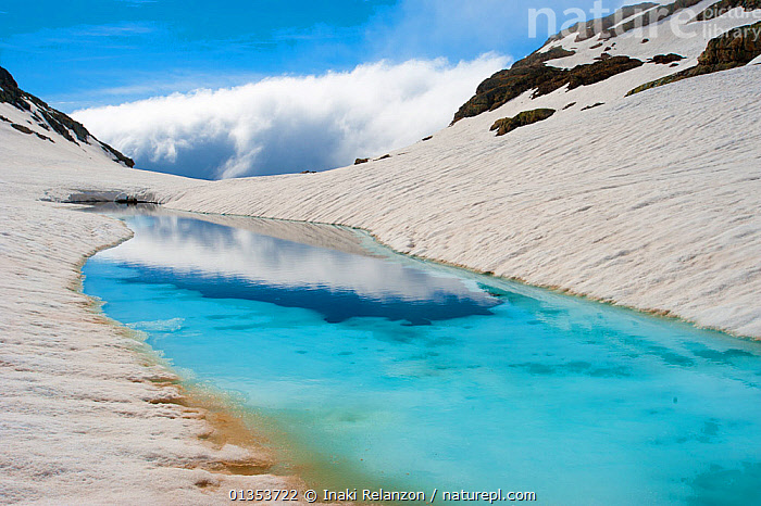 Blue ice melt pool in snow near the peak of La Munia Circo. The Pyrenees, Aragon, Spain, May 2011.  ,  Aragon,BLUE,catalogue4,CLOUDS,ENVIRONMENTAL,EUROPE,ICE,LANDSCAPES,melt,melt pool,Mountain,mountain peak,MOUNTAINS,Mountainside,nature,Nobody,NP,pool,pyrenees,reflection,RESERVE,Scenic,SNOW,SPAIN,thaw,WATER,WINTER,wonderland,Weather,National Park  ,  Inaki Relanzon
