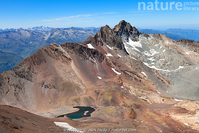 Gourg de Cap de Long, a mountain tarn with the summits of Pic de Maoli with Pic de Badet behind. Viewed from summit of Pic de Campbiel, Hautes-Pyrenees, France, August.  ,  ALPS,BLUE,EUROPE,FRANCE,LAKES,LANDSCAPES,MOUNTAINS,PEAKS,PLANTS,SCENIC,SKY,SNOW,WATER  ,  Alex Hyde