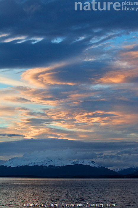 Evening sun catching the clouds with snow-clad mountains. Beagle Channel, Tierra del Fuego Archipelago, South America, December.  ,  ATMOSPHERE,CLOUDS,COASTS,LANDSCAPES,MOUNTAINS,PATAGONIA,SEACAPES,SEASCAPES,SKIES,SOUTH AMERICA,TIERRA DEL FUEGO,VERTICAL,Weather,SOUTH-AMERICA  ,  Brent Stephenson