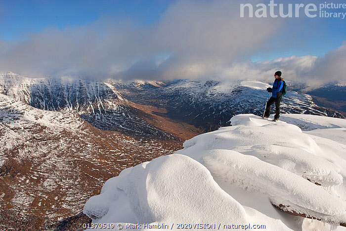 Hillwalker admiring the view from the summit of Tom na Gruagaich in winter, Beinn Alligin, Torridon, Scotland, UK, February 2010 Model Released. 2020VISION Exhibition. 2020VISION Book Plate. Did you know? The name Beinn Alligin comes from the Scottish Gaelic for Jewelled Hill., 2020VISION,2020vision book plate,2020vision exhibition,picday,Caucasian,CLOUDS,COLD,EUROPE,exhibition,HIGH ANGLE SHOT,HIGHLANDS,hiking,LANDSCAPES,MOUNTAINS,one person,outdoors,PEOPLE,SCOTLAND,SNOW,summit,summits,UK,UPLANDS,WHITE,WINTER,WOMAN,Weather,United Kingdom,2020cc, Mark Hamblin / 2020VISION
