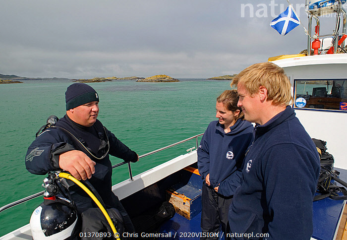 Underwater photographer Alex Mustard on board Sea Life Surveys boat Sula Crion preparing to dive at the Cairns of Coll, watched by two tourist guides, Inner Hebrides, Scotland, UK, July 2011  ,  ABOARD,BOATS,COASTAL WATERS,EUROPE,OUTDOORS,THREE,WORKING BOATS,2020VISION,DIVING,PEOPLE,SCOTLAND,SEAS,UK,United Kingdom  ,  Chris Gomersall / 2020VISION