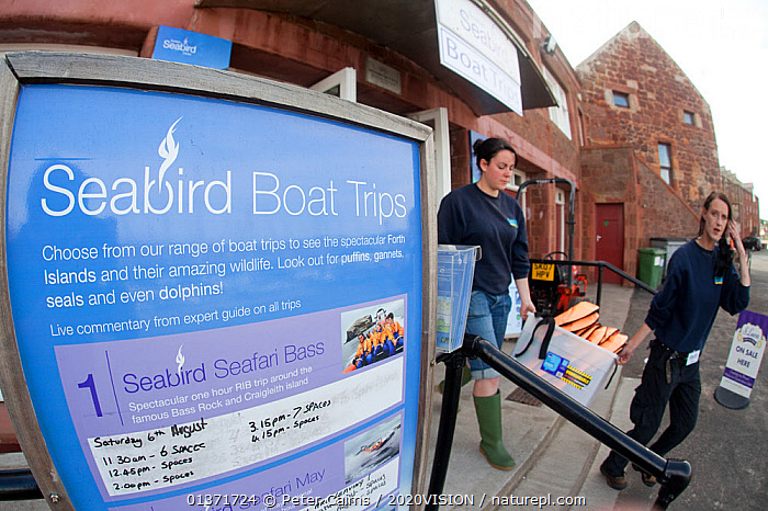 Sign detailing tourist boat trips at Scottish Seabird Centre, North Berwick, Scotland, UK, August 2011  ,  CAUCASIAN,COASTAL WATERS,ECO TOURISM,EUROPE,OUTDOORS,SIGNS,TWO,WOMEN,2020VISION,ECOTOURISM,LEISURE,PEOPLE,SCOTLAND,SEAS,TOURISM,UK,United Kingdom  ,  Peter Cairns / 2020VISION