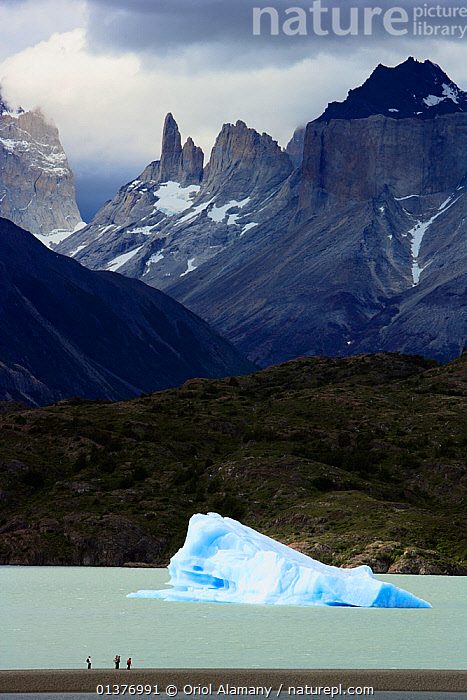 People and an iceberg in Lake Grey with Valle del Frances in the background, Torres del Paine National Park, Patagonia, Chile, Andes,catalogue4,chile,COLD,elevated view,HIGHLANDS,iceberg,imposing,Lake,Lake Grey,LAKES,majestic,MEN,mid adult,MOUNTAINS,national park,NP,patagonia,PEOPLE,RESERVE,SCALE,SOUTH AMERICA,STANDING,storm cloud,three people,Torres del Paine,tourists,Travel,Valle del Frances,VERTICAL,view from above,view to land,WATER,SOUTH-AMERICA, Oriol Alamany