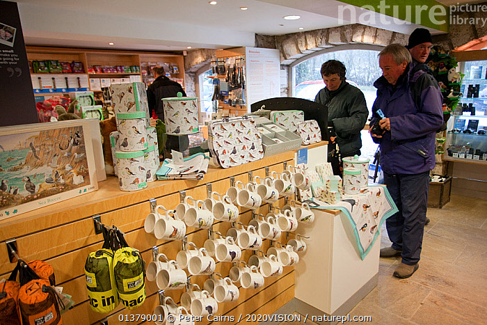 Shop at RSPB Leighton Moss visitor centre, showing economic benefits of wildlife tourism, Morecambe Bay, Cumbria, England, UK, February  ,  BIRDWATCHING,CAUCASIAN,COASTS,EUROPE,INDOORS,MEN,SHOP,WOMAN,2020VISION,BIRD WATCHING,ENGLAND,FOUR,LEISURE,PEOPLE,RESERVE,SHOPS,TOURISM,TRADE,UK,United Kingdom  ,  Peter Cairns / 2020VISION