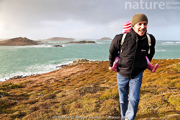 Man carrying child along footpath on a stormy day on St. Martin's, Isles of Scilly, UK, January 2012. No release available.  ,  CARRYING,carrying on back,catalogue5,child,CHILDREN,cliff,coastal,COASTS,Cornwall,daughter,ENGLAND,ENJOYMENT,EUROPE,exploration,father,footpath,FOOTPATHS,girl,hiking,ISLANDS,Isles of Scilly,LANDSCAPES,LEISURE,MAN,mid adult,nature,outdoors,PEOPLE,sea,St Martins,stormy,two people,UK,United Kingdom  ,  Merryn Thomas