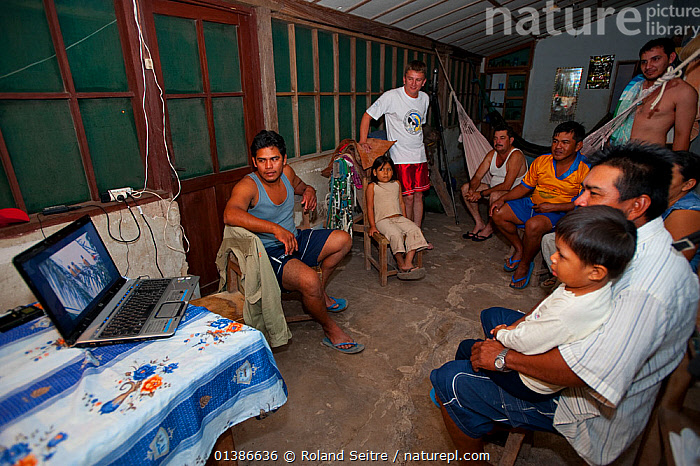People gathered in front of laptop computer watching an educational programme on the conservation of the Blue throated / Wagler's macaw (Ara glaucogularis) Santa Ana del Yacuma, Beni, Bolivia, Critically endangered species, July 2008.  ,  BIRDS,CANIDE MACAW,CHILDREN,CONSERVATION,CRITICALLY ENDANGERED,EDUCATION,ENDANGERED,FAMILIES,GROUPS,HISPANIC,INDOORS,MACAWS,PARROTS,PEOPLE,PSITTACIDAE,SOUTH AMERICA,VERTEBRATES,WAGLER'S MACAW  ,  Roland Seitre