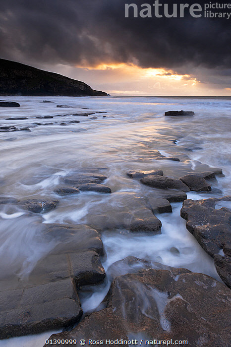 View of Southerndown with dark storm clouds overhead, Glamorgan Heritage Coast, near Bridgend, Wales, UK, December 2012.  ,  CLOUDS,COASTS,EUROPE,GEOLOGY,LANDSCAPES,ROCKS,STORMS,SUN,TIME EXPOSURE,UK,VERTICAL,WATER,WEATHER,United Kingdom  ,  Ross Hoddinott