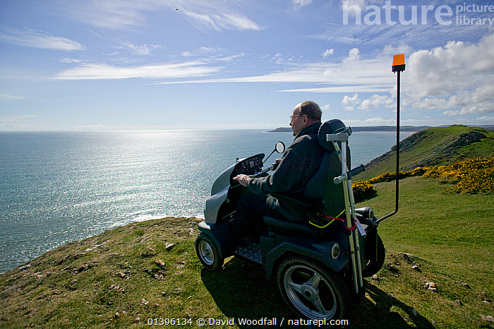 Disabled Man in his 80's enjoying stunning coastal scenery from Pennard cliff using 'Tramper ' machine designed to aid mobility to difficult places for disabled people, Gower, South Wales, UK 2009  ,  ACCESS,CLIFFS,COASTLINE,COASTS,DISABILITY,EUROPE,LANDSCAPES,MARINE,PEOPLE,PROFILE,SEA,SOUTH WALES,TRANSPORT,UK,VIEWS,WALES,WATCHING,WHEELCHAIR,Geology,United Kingdom  ,  David Woodfall