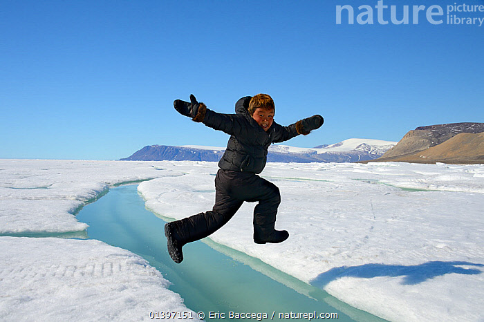 Young Inuit boy jumping over a crack on ice floe, Ellesmere Island, Nanavut, Canada, June 2012. Model released., ARCTIC,BOY,CANADA,CHILDREN,CLIMATE CHANGE,CONCEPTS,FROZEN,GLOBAL WARMING,ICE,INUIT,JUMPING,NORTH AMERICA,OUTDOORS,PEOPLE,PLAYING,SEA,SUMMER,TRIBES,Catalogue5, Eric Baccega
