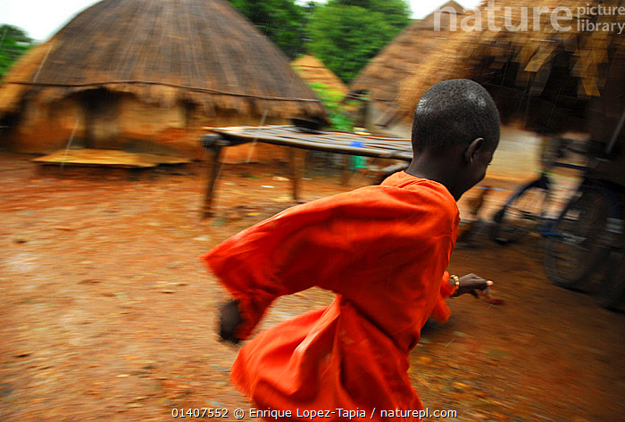 A boy runs in the rain in a Bassari village. Bassari country, east Senegal. This area became a UNESCO World Heritage site in 2012, for cultural landscape and traditions kept by the the Bassari, Fula and Bedik peoples. September 2006. Lux Awards Competition 2012.  ,  AFRICA,BOY,CHILDREN,CULTURES,PEOPLE,RAIN,RUNNING,TRIBES,VILLAGES,WEST AFRICA,Lux Awards 2012  ,  Enrique Lopez-Tapia