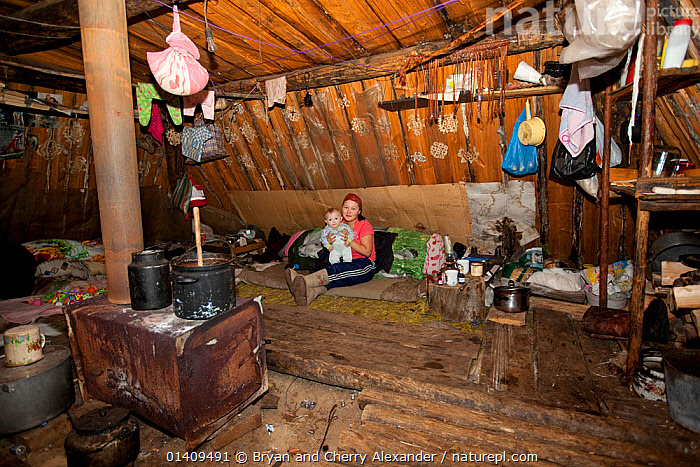 Lena Kuboleva, a young Selkup woman, with her daughter Violetta, inside a 'Poymot', (traditional Selkup turf winter hut), at a winter hunting camp in the forest near Ratta, Krasnoselkup, Yamal, Western Siberia, Russia 2012, ACCOMMODATION,ARCTIC,ASIA,BABIES,CAMPING,CAMPS,CHILDREN,CIS,CULTURES,FEMALES,HOMES,HUTS,INDIGENOUS,INTERIOR,JUVENILE,LIFESTYLE,MOTHER,MOTHER AND YOUNG,NATIVE,NOMADIC,PEOPLE,RUSSIA,SEASONAL,SELKUP,SIBERIA,TRADITIONAL,TRIBAL,TRIBES,WESTERN SIBERIA,WINTER,WOMAN,YOUNG, Bryan and Cherry Alexander