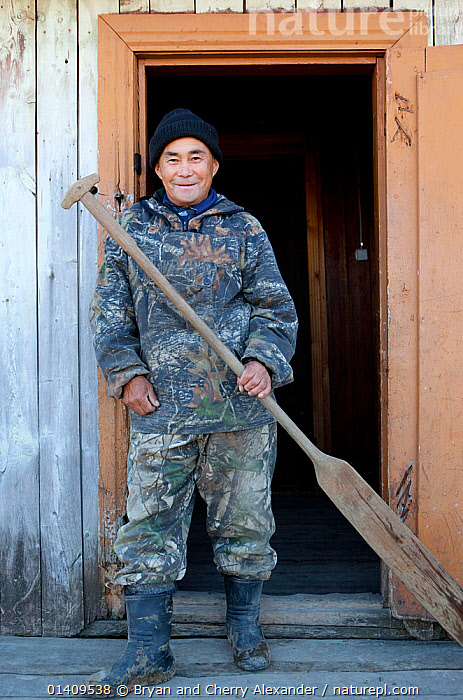 Andrey Kargochev, a Selkup elder, prepares to go hunting by boat, Tolka, Krasnoselkup, Yamal, Western Siberia, Russia, ARCTIC,ASIA,BUILDINGS,CIS,CULTURES,HOMES,HUNTER,INDIGENOUS,MALES,MAN,NATIVE,OAR,PADDLE,PEOPLE,PORTRAITS,RUSSIA,SELKUP,SIBERIA,STANDING,TRADITIONAL,TRIBAL,TRIBES,VERTICAL,WESTERN SIBERIA, Bryan and Cherry Alexander
