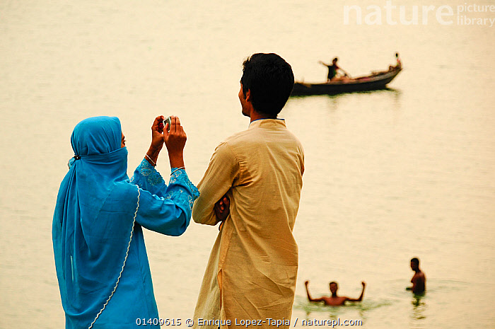Man and veiled woman taking a photograph of the  River Ganges at sunset, Rajshahi. Bangladesh  June 2012. No release available., ASIA,BANGLADESH,BOATS,COUPLE,COUPLES,FISHING BOATS,GANGES,MAN,PEOPLE,PHOTOGRAPHY,RIVERS,SUNSET,TRADITIONAL,WOMAN,INDIAN-SUBCONTINENT,Catalogue5, Enrique Lopez-Tapia