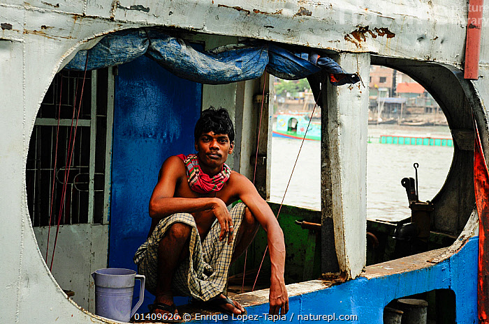 Man looking out from a boat at Sadarghat water front, Dhaleshwari river. Dhaka, Bangladesh. June 2012., ASIA,BANGLADESH,BOATS,CITIES,DOCKS ,MAN,MS,PEOPLE,RIVERS,URBAN,WORKING BOATS,INDIAN-SUBCONTINENT, Enrique Lopez-Tapia