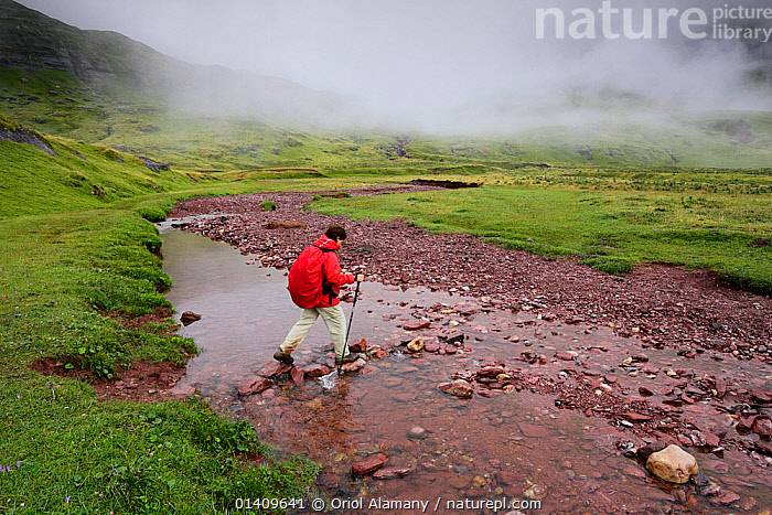 Woman hiking  on a rainy day, crossing a river in the Aguas Tuertas in Hecho valley, Los Valles Occidentales Natural Park, Pyrenees, Aragon, Spain. Model released., EUROPE,FOG,LANDSCAPES,MIST,RESERVES,SPAIN,STREAM,WALKING, Oriol Alamany