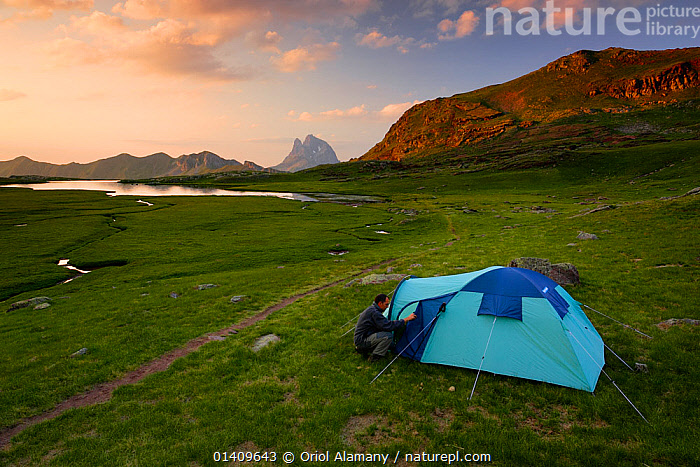 Hiker attending to tent while camping on Anayet alpine lakes. Midi d'Ossau peak in the background in Alto Gallego, Pyrenees, Aragon, Spain. Model released., ALPINE,CAMPING,EUROPE,LAKES,SPAIN,TENTS,TOURISM, Oriol Alamany