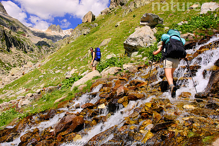 Women hiking,  crossing a stream in Remuae valley, Posets-Maladeta Natural Park, Pyrenees, Huesca, Aragon, Spain. Model released., EUROPE,LANDSCAPES,MOUNTAINEERING,MOUNTAINS,PEOPLE,RESERVE,SPAIN,STREAMS,TREKKING,WALKING,WOMEN,SPORTS, Oriol Alamany
