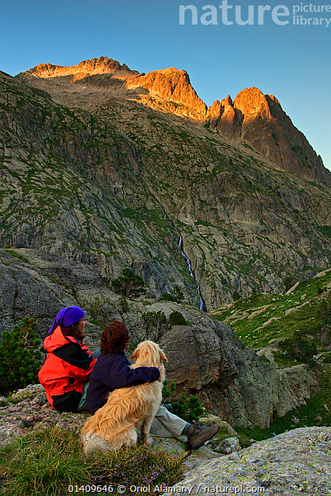 Two women hikers sitting with a Montana de los Pirineos domestic dog  at sunset watching the Remuae Valley, Parque Natural Posets-Maladeta Ribagorza, Pyrenees Huesca, Aragon, Spain. Model released., DOGS,EUROPE,HIKING,LANDSCAPES,MOUNTAINEERING,MOUNTAINS,OUTDOORS,PEOPLE,PETS,RESTING,SPAIN,TREKKING,VERTICAL,WOMEN,SPORTS, Oriol Alamany