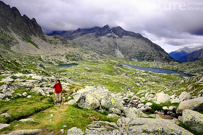 Woman hiker  walking the 'Carros de Foc' trail at Cirque de Travessani with Punta Alta peak (3013 m), Boi valley, Aiguestortes i Estany de Sant Maurici National Park, Pyrenees, Catalonia, Spain. Model released, EUROPE,FEMALE,HIKING,LAKES,LANDSCAPES,MOUNTAINEERING,MOUNTAINS,PEOPLE,SPAIN,TREKKING,WALKING,WOMAN,SPORTS, Oriol Alamany