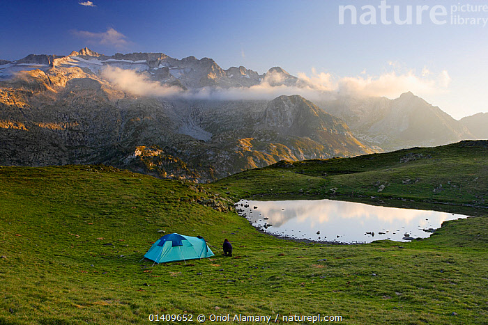 Mountaineer setting up camp below La Picada pass, with Aneto (3404 m) and Maladeta (3308 m) peaks with its glaciers in the massif of Maladeta in the background, Posets-Maladeta Natural Park, Pyrenees, Aragon, Spain, CAMPING,EUROPE,FEMALES,HIKING,LAKES,LANDSCAPES,MOUNTAINS,PEOPLE,SPAIN,TENT,TREKKING,WALKING, Oriol Alamany