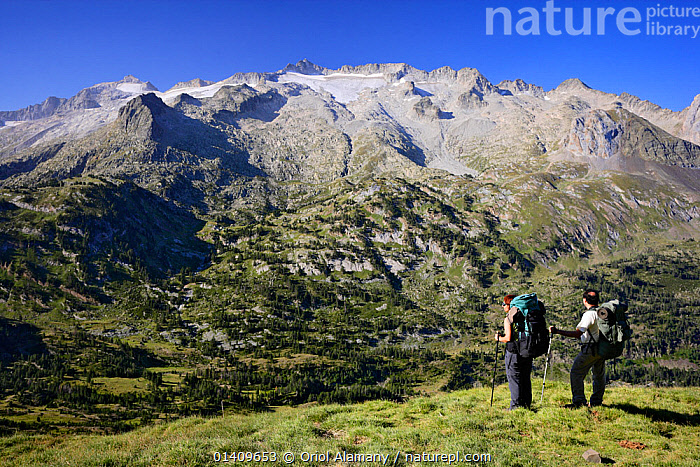 Two mountain walkers near La Picada pass, with Aneto Peak (3404 m) and Maladeta (3308 m) with its glaciers in the massif of Maladeta in the background, Posets-Maladeta Natural Park, Pyrenees, Aragon, Spain. Model released., EUROPE,HIKING,LANDSCAPES,MOUNTAINS,PEOPLE,RESERVE,SPAIN,TREKKING,WALKING, Oriol Alamany
