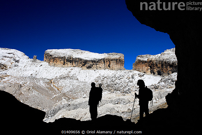 Two hikers silhouetted in Casteret ice cave with Brecha de Rolando / Roland's breach in the background, Ordesa and Monte Perdido National Park, Pyrenees, Aragon, Spain, EUROPE,HIKING,ICE,LANDSCAPES,MOUNTAINS,NP,PEOPLE,PYRENEES,RESERVE,SILHOUETTES,SNOW,SPAIN,WALKING,National Park,,UNESCO World Heritage Site,, Oriol Alamany