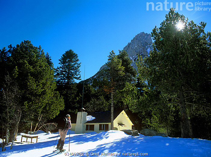Hiker with snowshoes arriving at Ernest Mallafre mountain hut, Aiguestortes i estany de Sant Maurici National Park, Catalonia, Pyrenees, Spain, Model released., COLD,EUROPE,MOUNTAINS,NP,PEOPLE,RESERVE,SNOW,SNOW SHOES,SPAIN,TREES,WINTER,National Park,PLANTS, Oriol Alamany