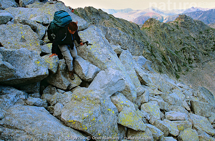 Hiker crossing a scree field in the Collada de Saburo Pass along the  'Carros de Foc' route,  Aiguestortes i Estany de Sant Maurici National Park, Pyrenees, Catalonia, Spain. Model released, EUROPE,HIKING,LANDSCAPES,MOUNTAINEERING,MOUNTAINS,PEOPLE,SPAIN,TREKKING,WALKING,WOMAN,WOMEN,SPORTS, Oriol Alamany