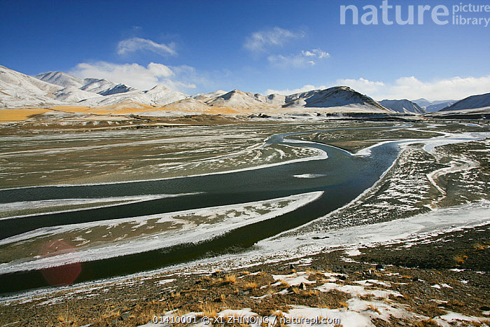 Landscape of Tibetan Plateau, with stream flowing through and mountains in the distance. Kekexili, Qinghai, Tibetan Plateau, China, December 2006, ASIA,BLUE SKY,CHINA,CLOUDS,HORIZON,HORIZONS,LANDSCAPES,MOUNTAINS,NOBODY,RIVERS,SKY,SNOW,STREAMS,TIBETAN PLATEAU,WINTER,Weather, XI ZHINONG