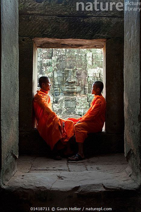 Two buddhist monks relaxing in the Bayon Temple, Angkor Wat, Siem Reap, Cambodia 2010. Model released.  ,  ancient,angkor,Angkor Wat,ASIA,Bayon Temple,buddhism,buddhist,CAMBODIA,catalogue5,CULTURES,face to face,full length,HISTORICAL,LANDSCAPES,MEN,men only,monks,OLD,orange colour,outdoors,PEOPLE,PORTRAITS,Religion,side view,Siem Reap,SITTING,SOUTH EAST ASIA,talking,temples,Travel,two people,VERTICAL,window,windows,young adult,young men  ,  Gavin Hellier
