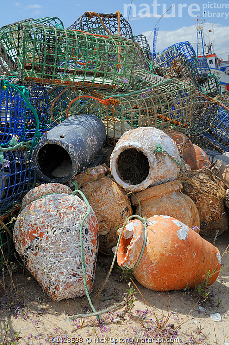 Stack of lobster pots and traditional ceramic Octopus pots encrusted with serpulid worm tubes and barnacles, Culatra island, Parque Natural da Ria Formosa, near Olhao, Algarve, Portugal, June.  ,  ARTIFACTS,EUROPE,FISHING,FISHING EQUIPMENT ,NP,PORTUGAL,POTS,TRADITIONAL,TRAPPING,TRAPS,VERTICAL,National Park  ,  Nick Upton