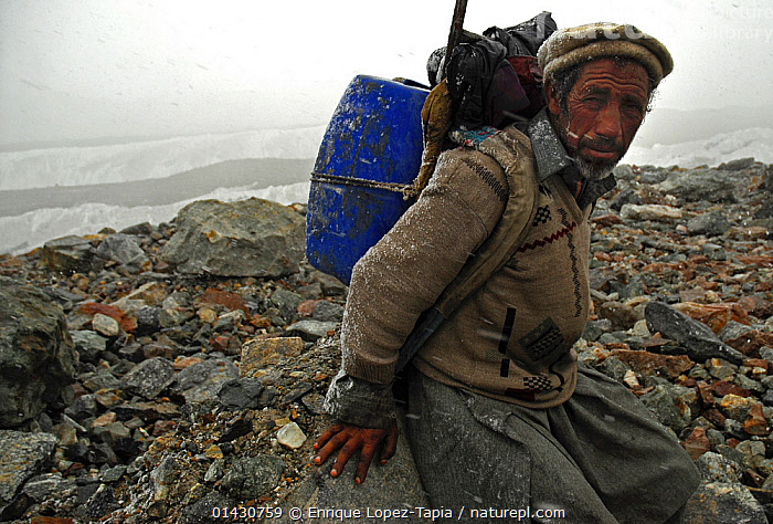 A Balti porter on the Baltoro Glacier, Concordia, Central Karakoram National Park, Pakistan, July 2007.  ,  ASIA,ASIAN ETHNICITY,ATMOSPHERIC,CARRYING,CLOUDS,GLACIERS,HIKING,HIMALAYA,HIMALAYAS,INDIAN SUBCONTINENT,KARAKORAM,LANDSCAPES,LOOKING AT CAMERA,MAN,MOUNTAINS,OUTDOORS,PEOPLE,PORTER,PORTRAITS,SNOW,SNOWING,TRADITIONAL,TREKKING,UPLANDS,WALKING,Weather,Geology  ,  Enrique Lopez-Tapia