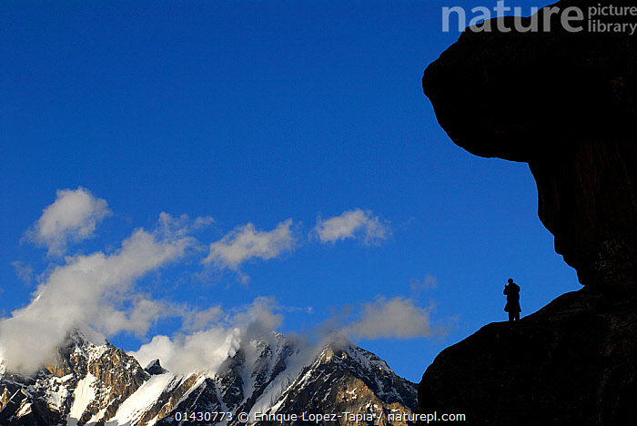 A Balti porter silhouetted standing on a rock, with mountains in the distance, Urdukas Camp (4,000m), Baltoro Glacier, Central Karakoram National Park, Pakistan, July 2007., ASIA,CLOUDS,HIMALAYA,HIMALAYAS,INDIAN SUBCONTINENT,KARAKORAM,LANDSCAPES,MAN,MOUNTAINS,NP,OUTDOORS,PEOPLE,RESERVE,ROCK FORMATIONS,SILHOUETTES,UPLANDS,Weather,National Park, Enrique Lopez-Tapia