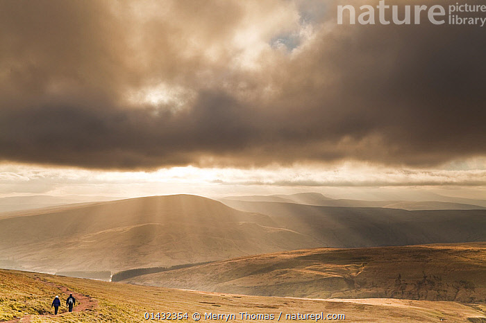 View over the Brecon Beacons with two people walking on a path, Brecon Beacons National Park, Powys, Wales, February 2012.  ,  ATMOSPHERIC,CLOUDS,EUROPE,OUTDOORS,PATH,REAR VIEW,UPLANDS,WALES,HIKING,LANDSCAPES,LEISURE,NP,PATHS,PEOPLE,RESERVE,UK,WALKING,Weather,National Park,United Kingdom  ,  Merryn Thomas