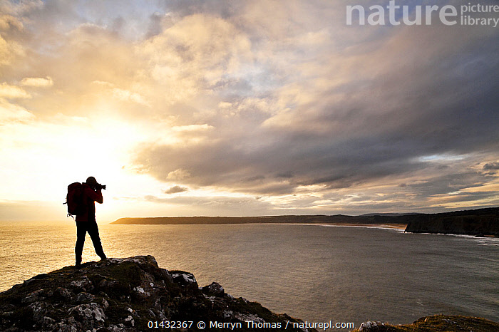 Man taking a photograph of Three Cliffs Bay and Oxwich Bay from above Pobbles Bay, Gower, Swansea, Wales, January 2013. Model released. (This image may be licensed either as rights managed or royalty free.)  ,  BEACHES,CLIFFS,COASTS,EUROPE,MAN,PHOTOGRAPHY,SUNSET,WALES,CAMERA,CAMERAS,GOWER,LANDSCAPES,PHOTOGRAPHER,SILHOUETTES,SUNRISE,UK,Geology,PEOPLE ,United Kingdom,,Journeyman,Travel,Wanderlust,,RF, royalty free, RF3,,RF3,,RF,  ,  Merryn Thomas