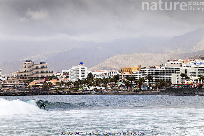 Man surfing, Playa de Las Americas, Tenerife, Canary Islands, Spain, March 2012.  ,  ATLANTIC ISLANDS,EUROPE,OUTDOOR PURSUITS,SPAIN,WATER PURSUITS,BUILDINGS,CANARY ISLANDS,LEISURE,PEOPLE,SURFING,TOURISM,TOWNS,SPORTS,WATERSPORTS  ,  Merryn Thomas