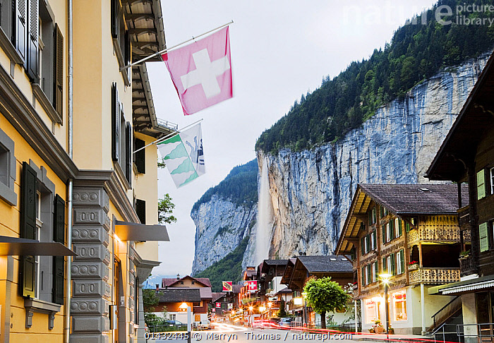 View of Lauterbrunnen village and waterfall, Bernese Oberland, Switzerland, June 2012., catalogue6,No One,Nobody,Europe,Western Europe,Switzerland,Diminishing Perspective,Man Made,Flag,Country Flag,National Flag,Swiss Flag,Swiss Flags,Settlement,Town,Towns,Village,Villages,Road,Urban Road,Street,Street Scene,Streets,Man Made Structure,Building,Building Exterior,Cliff,Light,Lights,Waterfall,Cascade,Cascades,Waterfalls,Outdoors,Open Air,Outside,Day,Architecture,Travel,Place Of Interest,Travel Destinations,Woodland,Forest,Bernese Oberland,Lit Light,Lauterbrunnen, Merryn  Thomas