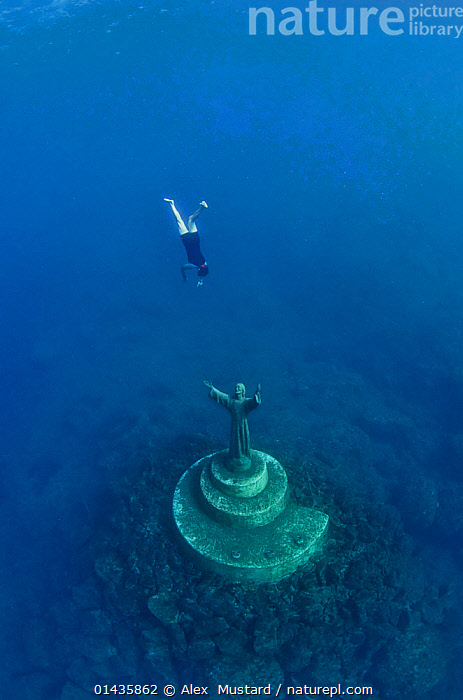 A fisherman swims down to touch the statue of Christ Of The Abyss (Cristo degli abissi) for good fortune, in the Marine Protected Area of Portofino (Area Marina Protetta, Portofino), Liguria, Italy. Mediterranean Sea.