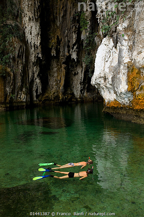 Two women snorkeling in front of the cave, Raja Ampat, Irian Jaya, West Papua, Indonesia, Pacific Ocean. Model released.  ,  catalogue6,Leisure,Snorkeling,Snorkelling,Snorkler,Snorklers,Snorkling,People,Female,Woman,Sayings,Getting Away From It All,Away From It All,2 People,Two Person,Two Persons,East Asia,South East Asia,Indonesia,Oceania,Melanesia,New Guinea,Vertical,Man Made,Object,Clothing,Sports Clothing,Swimwear,Swimming Costume,Bathing Suit,Bathing Suits,Swimming Costumes,Swimsuit,Swimsuits,Building,Entrance,Entrances,Cave,Ocean,Pacific Ocean,Outdoors,Open Air,Outside,Day,Exploration,Marine,Saltwater,Sea,West Irian Jaya,Irian Jaya,Biodiversity hotspots,Biodiversity hotspot,Discovery,Asia  ,  Franco  Banfi