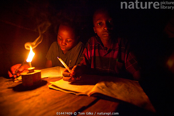 Tanzanian boys doing homework using oil lamp, Tanzania.  ,  catalogue6,Writing,Compose,Composes,Composing,Write,People,African Descent,Male,Sibling,Siblings,Brother,Brothers,Childhood,Chores,Chore,Task,Tasks,Homework,Home Work,Hardship,Poor,Inside,Side By Side,2 People,Two Person,Two Persons,Africa,East Africa,Tanzania,Animal,Lighting,Lamp,Electric Lamp,Electric Lamps,Lamps,Furnishing,Furniture,Table,Tables,Clothing,Shirt,Shirts,Light,Lights,Candlelight,Candlelights,Night,Nocturnal,Education,Educational,Environment,Environmental Issues,Power supply,Family,Energy,Developing countries,Children education,Development,Local people,Direct Gaze  ,  Tom  Gilks