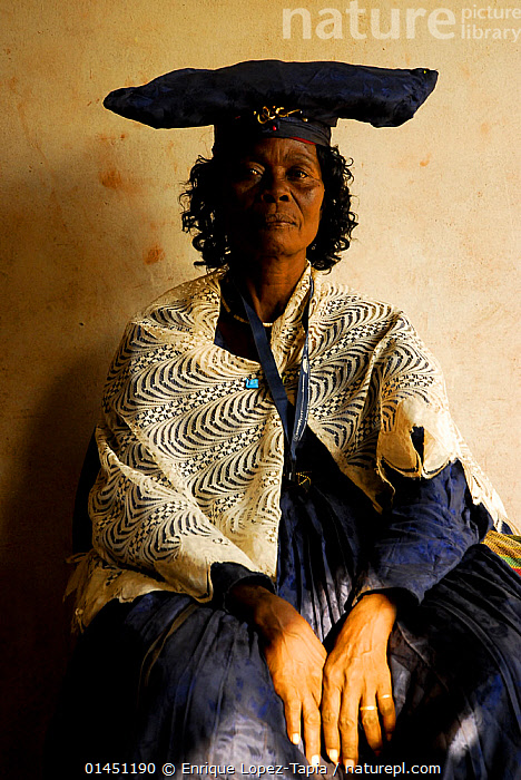 Herero woman in traditional dress - influenced by Victorian missionaries, Kaokoland, Namibia. February 2005  ,  catalogue7,Sitting,People,African Descent,Native African Ethnicity,Herero,Hereros,Herrero,Herreros,Female,Woman,Only Women,One Woman Only,One Woman,Pride,Proud,1 Person,Single,Single Person,Styles,19th Century Style,1800s,1800's,19th Century Styles,Nineteenth Century Style,Nineteenth Century Styles,Victorian,Serious,Africa,Southern Africa,Namibia,South-West Africa,Front View,View From Front,Portrait,Clothing,Headdress,Hat,Hats,Shawl,Shawls,Traditional Clothing,Indoors,Day,Fashion,Fashion And Clothing,Culture,African Culture,African,Indigenous Culture,Westernisation,Westernization,Tribes,Namibian,Kaokoland,Colonisation  ,  Enrique Lopez-Tapia