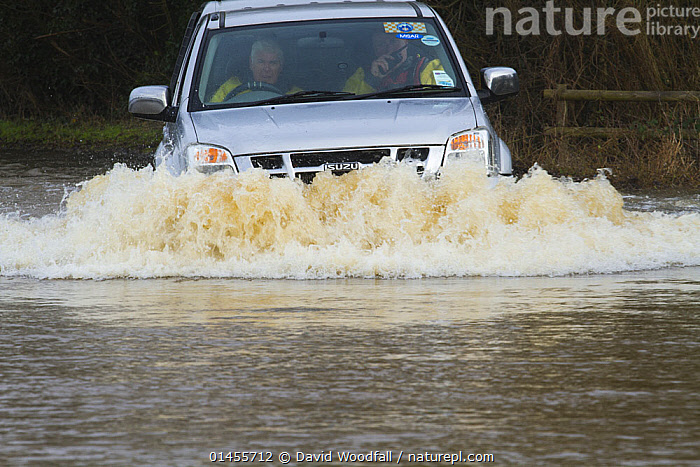 4X 4 travelling through floods carrying rescue workers during February 2014 flooding, Upton upon Severn, Worcestershire, England, UK, 9th February 2014., SPLASHING,EUROPE,WESTERN EUROPE,WEST EUROPE,UK,BRITAIN,GREAT BRITAIN,UNITED KINGDOM,ENGLAND,WORCESTERSHIRE,MODE OF TRANSPORT,VEHICLE,VEHICLES,LAND VEHICLE,LAND VEHICLES,MOTOR VEHICLE,AUTOMOTIVE,CAR,AUTOMOBILE,AUTOMOBILES,CARS,OFF ROAD VEHICLE,4X4,4X4S,FOUR BY FOUR,FOUR BY FOURS,JEEP,JEEPS,OFF ROAD VEHICLE,OFF ROAD VEHICLES,SPORTS UTILITY VEHICLE,SUV,SUVS,FLOODED,FLOODING,FLOODS,FLOODWATER,FLOODWATERS,WATER,WEATHER,ENVIRONMENT,ENVIRONMENTAL ISSUES,ENVIRONMENTAL ISSUE,GLOBAL WARMING,GREENHOUSE EFFECT,CLIMATE CHANGE, David  Woodfall