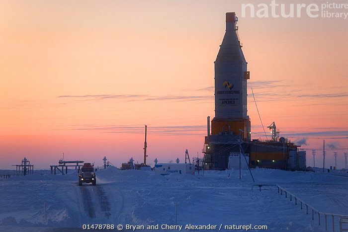 A gas drilling derrick at sunset in the South Tambey Gas Field, Yamal Peninsula, Siberia, Russia. February 2014.  ,  DRILLING,TEMPERATURE,COLD,CHILL,CHILLY,RUSSIA,SIBERIA,LAND VEHICLE,FOSSIL FUEL,FOSSIL FUELS,FUEL,FUELS,NATURAL GAS,NATURAL GASES,GAS,GASES,ICE,SNOW,SUNSET,SETTING SUN,SUNSETS,LANDSCAPE,LANDSCAPES,WINTER,ENVIRONMENT,ENVIRONMENTAL ISSUES,POWER SUPPLY,INDUSTRY,INDUSTRIAL,INDUSTRIES,PRODUCTION,ENERGY,DUSK  ,  Bryan and Cherry Alexander