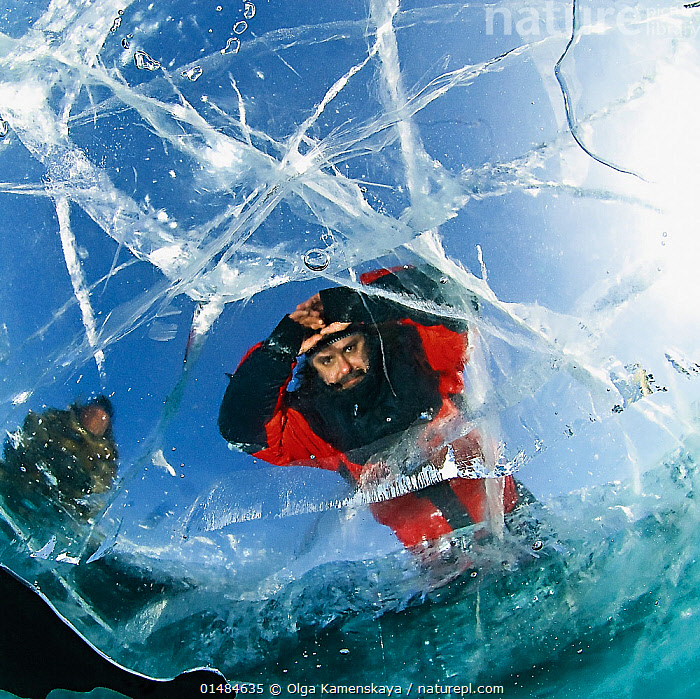 Man looking through transparent ice (1m thick) on lake surface to see diver below. Lake Baikal, Russia, March 2008. Model released.  ,  catalogue7,People,Male,Man,Only Men,Stalker,Stalkers,Mood,Trapped,Frozen,Below,Beneath,Under,Underneath,Cracked,Transparent,Waterproof,Temperature,Cold,Russia,Siberia,Low Angle View,Unusual Angle,Personal Perspective,Personal Perspectives,Pov,Sky,Ice,Outdoors,Open Air,Outside,Day,Freshwater,Lake,Underwater,Water,Lake Baikal,Blue sky,Looking Through,Personal POV,,Personal Point of View,  ,  Olga Kamenskaya