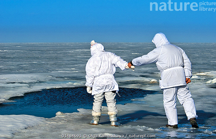 People looking at hole in ice used by Baikal seals (Pusa sibirica) for breathing. Lake Baikal, Russia, April 2009.  ,  PEOPLE,FROZEN,TEMPERATURE,COLD,CHILL,CHILLY,RUSSIA,SIBERIA,PHYSICAL STRUCTURE,HOLE,APERTURE,APERTURES,HOLES,ICE,FRESHWATER,LAKE,COLD WATER,LAKE BAIKAL,COLDWATER,SURFACE  ,  Olga Kamenskaya