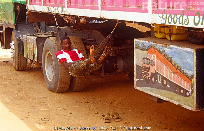 Hired man in hammock looking after truck from Nigeria, Niamey, Niger, 2005., Resting,Rest,Working,People,African Descent,Native African Ethnicity,Male,Man,Africa,West Africa,Niger,Furnishing,Furniture,Sleeping Furniture,Hammock,Hammocks,Land Vehicle,Motor Vehicle,Truck,Lorries,Lorry,Trucks,West African, Steve O. Taylor (GHF)