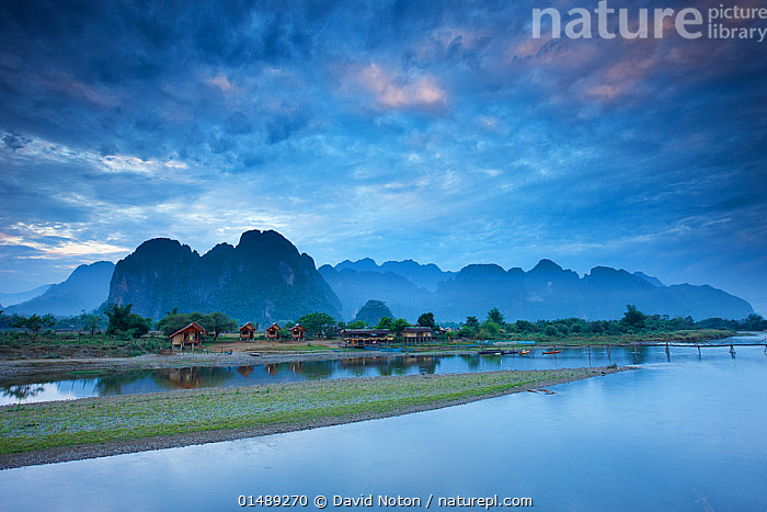 Dawn over the mountains and Nam Song River at Vang Vieng, Laos, March 2009.  ,  Spectacular,Mood,Calm,Morning,Mornings,Scale ,Proportion,Colour ,Blue,Nobody,North America,Asia,South East Asia,Laos,Lao People's Democratic Republic,Skyline,Skylines,Building,Residential Structure,House,Houses,Mountain,Rock,Limestone,Sky,Cloud,Flowing Water,River,Landscape,Landscapes,Outdoors,Open Air,Outside,Day,Beautiful,Nature,Natural,Natural World,Open Space,Open Spaces,Scenery,View,Views,Vista,Travel,Freshwater,Water,Dawn,View to land,Expansive,Blue Colour,Vang Vieng,Nam Song River,Moods,Buildings,Mountainous,Mountains,Rocks,Skies,Clouds,Rivers,Scenics,Colours,Colors, high15  ,  David Noton