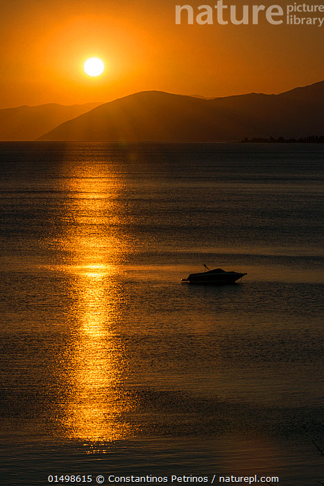 Sunset reflected on the surface of the Aegean Sea on a calm day with a speedboat, Evia Island, Greece. July 2014., high15,,,Atmospheric Mood,Atmospheric,Mood,Calm,Idyllic,Idylic,Alone,Silence,Quiet,Solitude,Solitary,Colour,Yellow,Nobody,Luminosity,Glow,Glows,Europe,Southern Europe,Greece,Vertical,Boat,Boats,Motorboats,Powerboats,Speedboat,Speed Boat,Speedboats,Peninsula,Promontory,Island,Islands,Reflection,Mediterranean Sea,Aegean Sea,Aegean,Sunset,Setting Sun,Sunsets,Outdoors,Open Air,Outside,Twilight,Evening,Coast,Marine,Water Surface,Coastal,Water,Motorboat,Saltwater,Sea,Mediterranean Basin,Mediterranean,Biodiveristy hotspot,Dusk,View to land,Yellow Colour,Evia Island,, Constantinos Petrinos