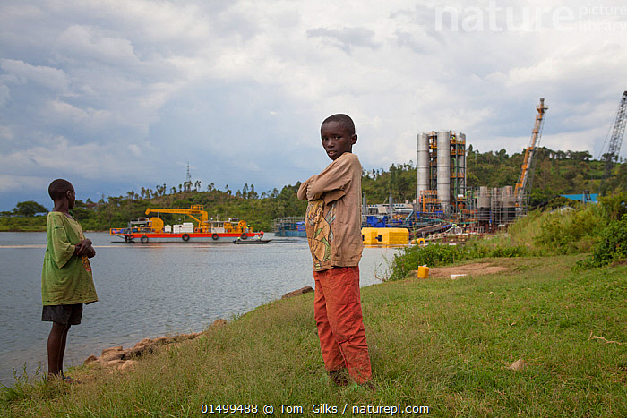 Two children standing in front of Kivuwatt biogas plant under construction. The plant will remove methane from the waters of Lake Kivu and power three genrators to produce 26MW of electricity. Kibuye, Rwanda, November 2014.  ,  PEOPLE,CHILD,TWO,AFRICA,EAST AFRICA,RWANDA,REPUBLIC OF RWANDA,BUILDING,INDUSTRIAL BUILDING,CONSTRUCTION,ENVIRONMENT,ENVIRONMENTAL ISSUES,SUSTAINABLE RESOURCES,SUSTAINABILITY,POWER SUPPLY,ELECTRICITY,ELECTRIC,ELECTRICAL,SUSTAINABLE POWER,ENERGY,BIOFUEL,BIO FUEL,RENEWABLE  ,  Tom  Gilks