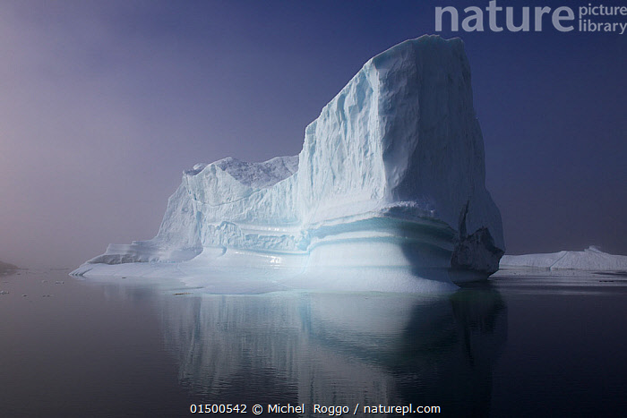 Iceberg in the sea outside the Kangia Ilulissat Icefjord. Iceberg from the Sermeg Kujalleg Glacier, UNESCO World Heritage Site, Kalaallit Nunaat, Greenland, August 2014. Photographed for The Freshwater Project.  ,  catalogue7,Atmospheric Mood,Atmospheric,Majestic,Mood,Calm,Mystery,Mysterious,Scale,Proportion,Silence,Quiet,Colour,Purple,White,Nobody,Dark,Darkness,Size,Giant,Huge,Massive,Large,Big,Temperature,Cold,Copy Space,Reflection,Ice,Glacier,Glacial,Glaciers,Ice Formation,Iceberg,Icebergs,Environment,Environmental Issues,Global Warming,Greenhouse Effect,Nature,Natural,Natural World,Beauty In Nature,Marine,Water,Cold Water,Saltwater,Sea,Climate change,Protected area,UNESCO World Heritage Site,UNESCO,Heritage Site,World Heritage site,Coldwater,Negative space,Freshwater Project,White colour,Imposing,Sea ice,Kalaallit Nunaat,Kangia Ilulissat,Icefjord,Sermeg Kujalleg,Wonder,Spectacular,  ,  Michel  Roggo